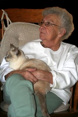 Senior Woman Holding Siamese Cat photo