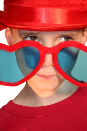 conflicted: Boy Peeking Hesitantly Over Heart-Shaped Glasses