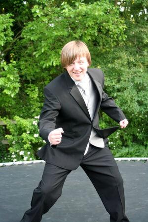 Tuxedo Teen Jumping On Trampoline photo
