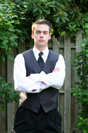 unyielding: Serious Prom Boy With Arms Folded Stock Photo