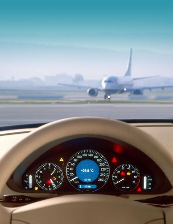 dash: Wheel and dashboard of a car and view of airport