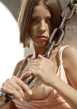 stubbornness: portrait of young woman with chain near the sea-front Stock Photo