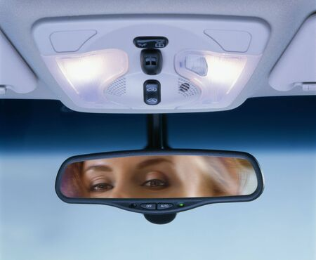 Young woman sits on drivers seat and Looks in the rear-view mirror Stock Photo