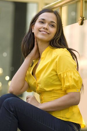 beautiful young woman in yellow blouse sits on the street photo