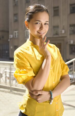 beautiful city woman in yellow blouse stands on the street photo