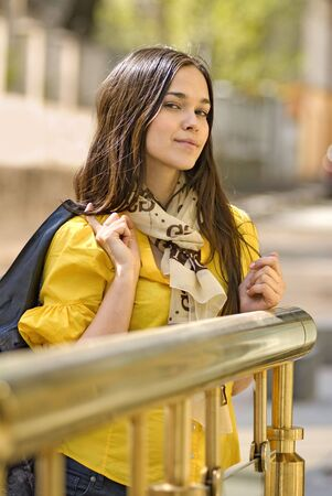 beautiful young woman in yellow blouse stands on the street photo