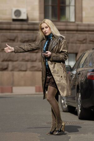 catching taxi: The beautiful blonde on roads catching taxi on a roadside.