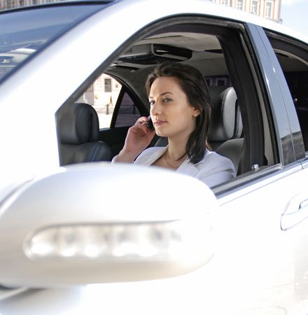 beautiful businesswoman talking on cellphone inside a white car photo