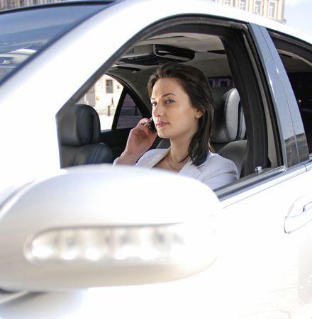 sexy business women: beautiful businesswoman talking on cellphone inside a white car
