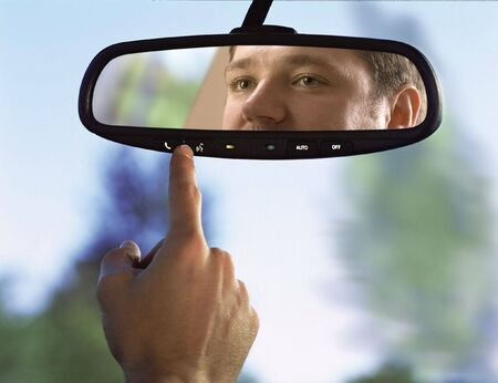 man sits on drivers seat and Looks in the rear-view mirror Stock Photo