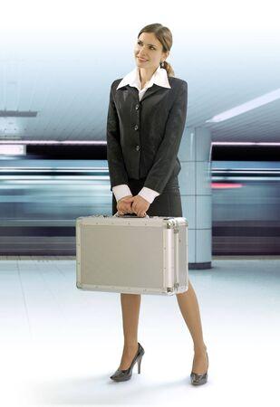 llegar tarde: businesstrip de la mujer joven feliz con plata maleta por metro  Foto de archivo