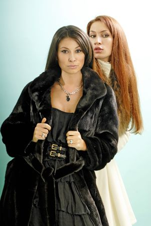 Portrait of two attractive young women with creativity hairstyle in fur coats photo