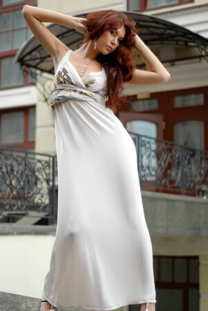 carnal: sexy brunette in long dress standing near old-fashioned hotel