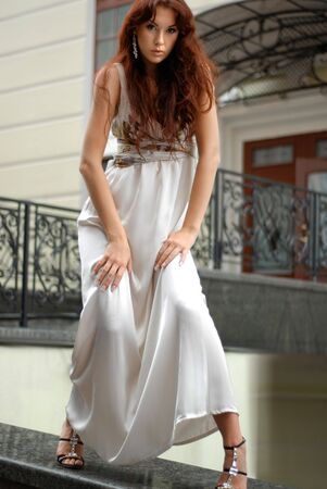showy: sexy brunette in long dress standing near a hotel