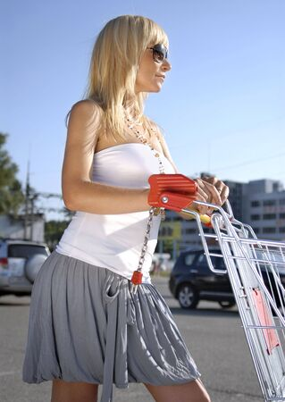 beautiful blonde woman with handcart near a supermarket Stock Photo - 5135670