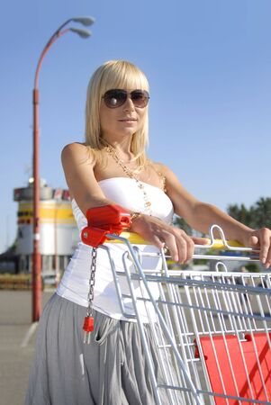 beautiful blonde woman with handcart near a supermarket Stock Photo - 5143973