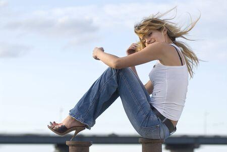 debility: beautiful happy blond woman near a river in jeans