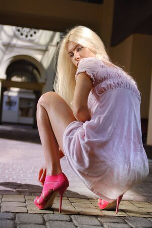 german girl: blond beautiful girl in pink shoes and dress  Stock Photo