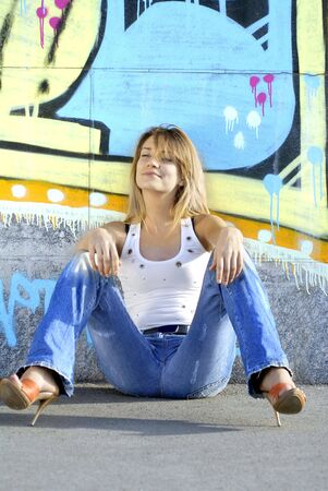 sexy blonde girl in jeans near color wall Stock Photo