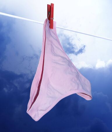 dangling: pink pants on the clothes-line and red clothes-peg