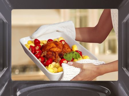 microwaves: hands of woman is taking out chicken with potato from oven Stock Photo