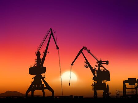 Two cranes sit dramatically against a colorful sunset in a large shipyard photo
