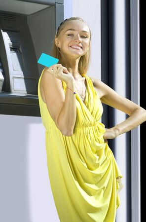 Attractive young woman withdrawing money from credit card at ATM photo
