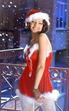 Portrait of beautiful sexy girl wearing santa claus clothes on winter city background photo
