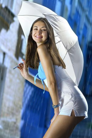 beautiful woman with white umbrella and light rain on a street of city Stock Photo - 5555691