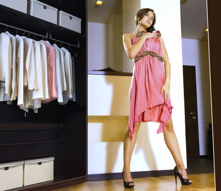 trying on: beautiful woman fits on a pink dress in the shopping mall
