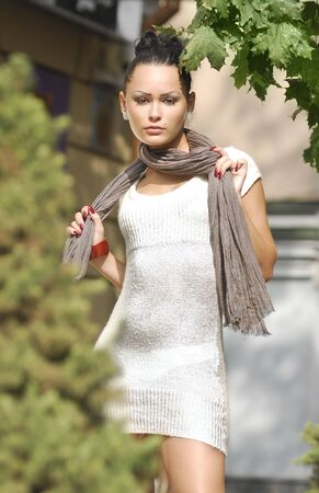 unmarried: Beautiful young woman in autumnal city in white dress Stock Photo