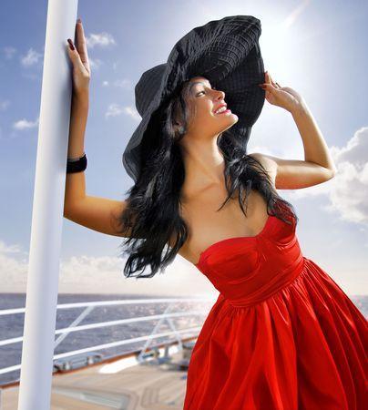 happy rich woman: bella donna in cuffia nera sullo yacht vicino a una spiaggia Archivio Fotografico