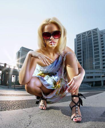 Beautiful blonde woman on urban background smoking cigaret