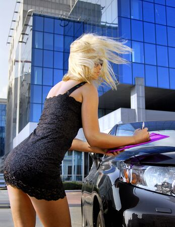beautiful blonde businesswoman writing something near her car photo