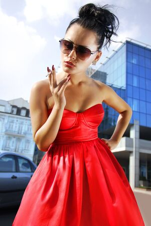 beautiful overweening brunette woman with cigarette near a business building photo