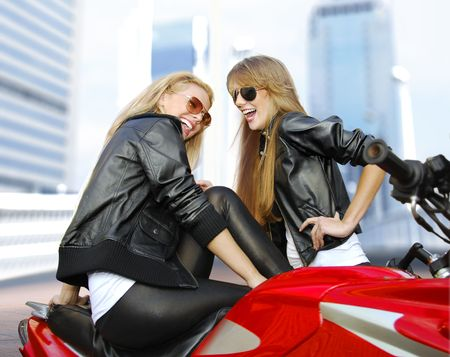 cheery: two cheery beautiful blonde motorcyclists and red motorcycle