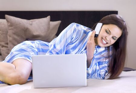 beautiful lady speaks to somebody by telephone on a bed photo