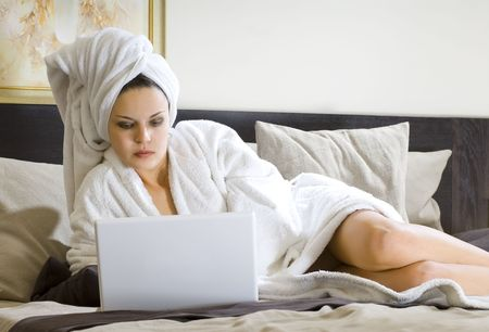 beautiful woman in white bathrobe on a bed with laptop photo