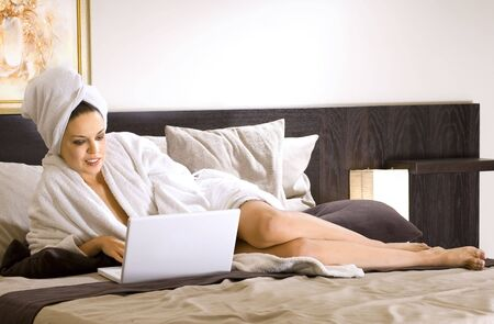 beautiful woman in white bathrobe on a bed with laptop Stock Photo - 5677267
