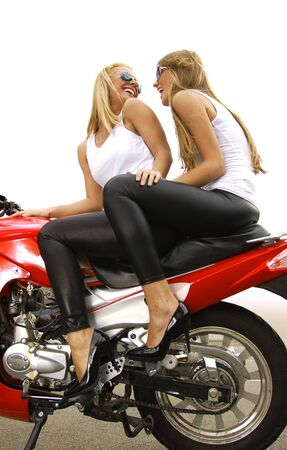 two pretty blonde woman on a big red motorcycle photo