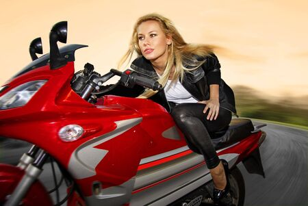 pretty blonde woman on a big red motorcycle photo