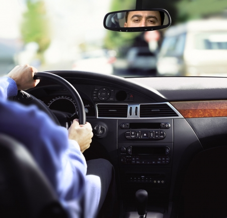 car dashboard: man sits on drivers seat and Looks in the rear-view mirror Stock Photo