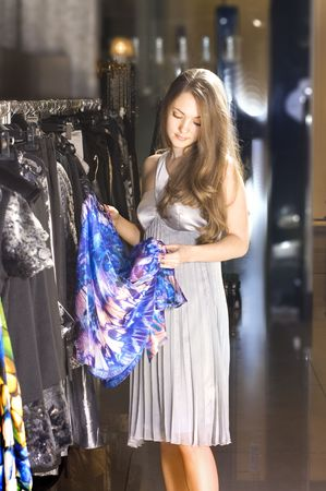beautiful rich woman chooses a dress in a boutique photo
