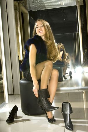 beautiful girl fits on a boots in a boutique Stock Photo - 5765142