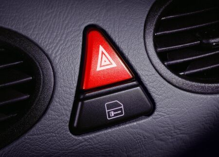 peril: red emergency button on a dashboard of car Stock Photo
