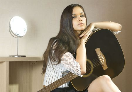 beautiful young lady in a room with guitar photo