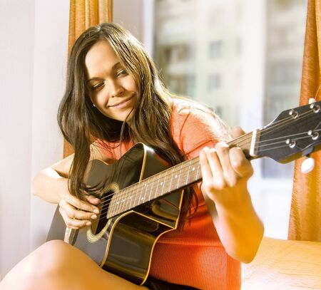 beautiful young lady in a room with guitar Stock Photo - 5788474