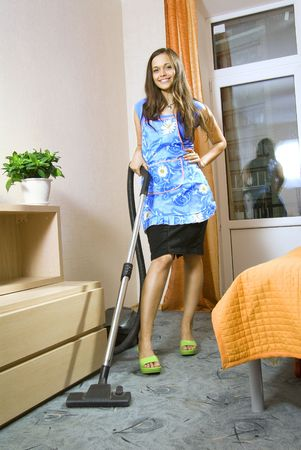 aprons: beautiful young housewife with vacuum cleaner in a room