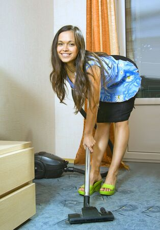 charlady: beautiful young housewife with vacuum cleaner in a room