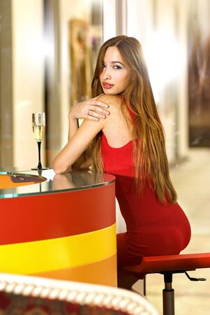 single woman: beautiful single woman in red dress with glass of champagne Stock Photo